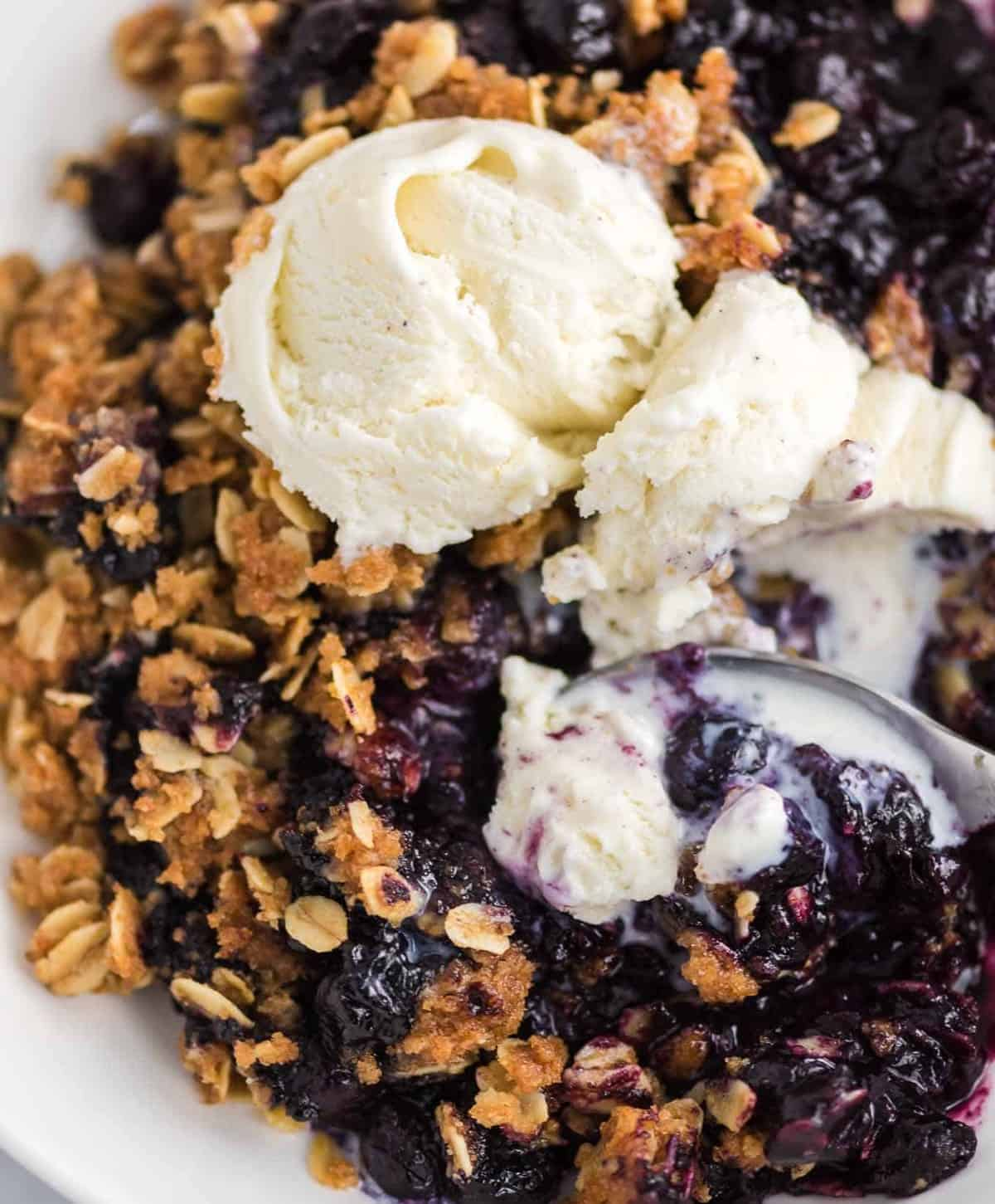 a silver spoon taking a bite of blueberry crisp and ice cream