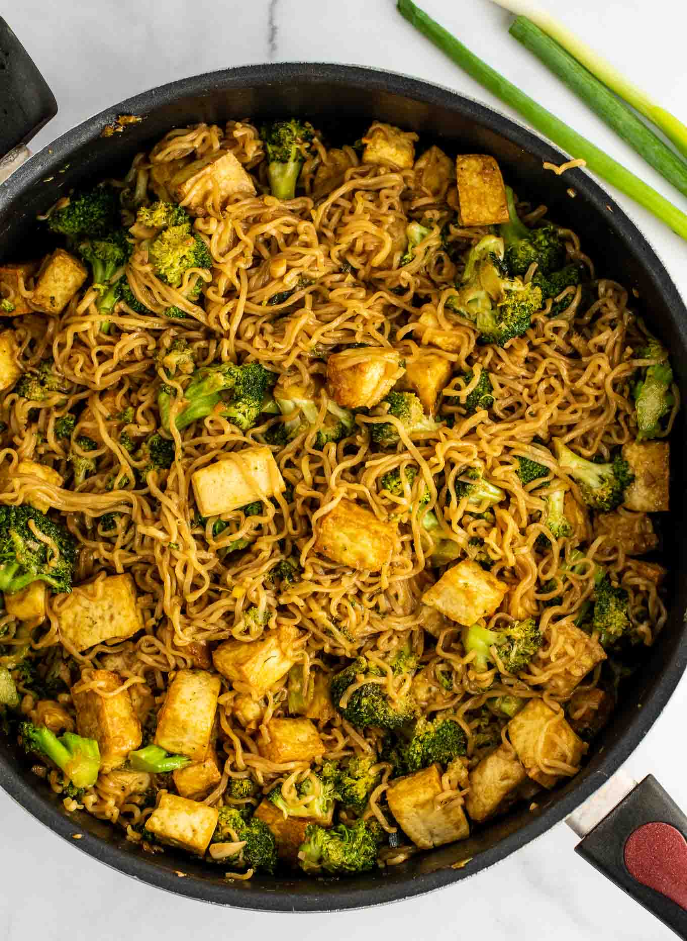ramen noodles in a skillet with tofu and broccoli