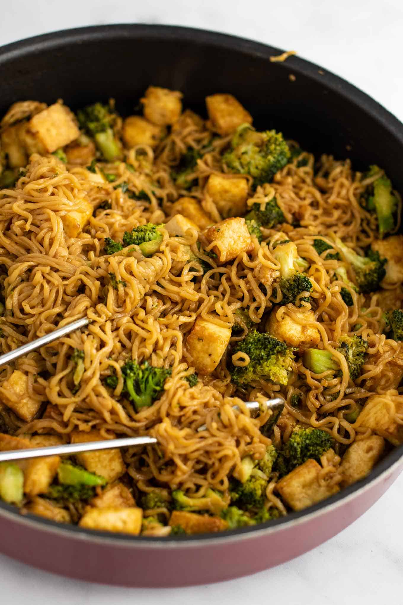 ramen noodle broccoli tofu stir fry in a pan from a side view