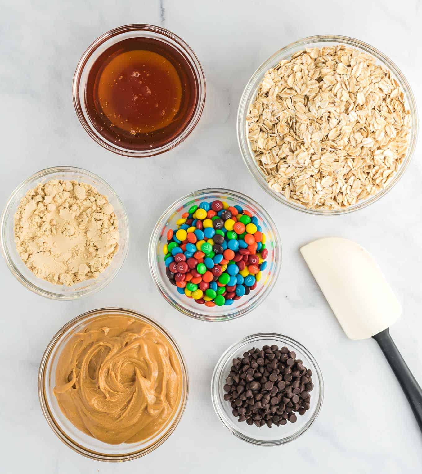 the ingredients in separate clear bowls - peanut butter, honey, protein powder, rolled oats, mini chocolate chips, and mini m&m's