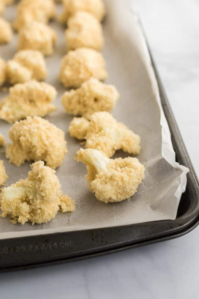 breaded cauliflower bites on a parchment paper lined baking sheet