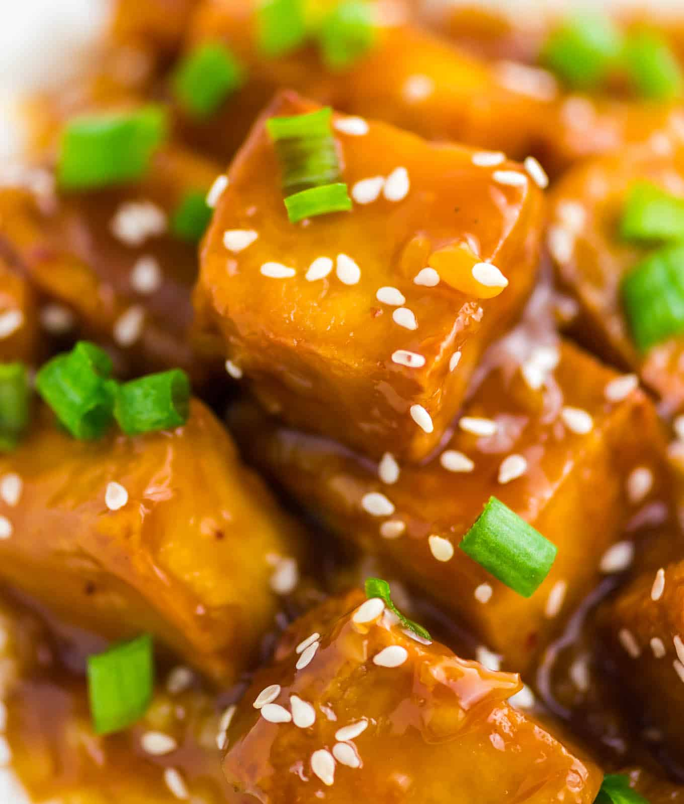 orange tofu over white rice with white sesame seeds and chopped green onions on top