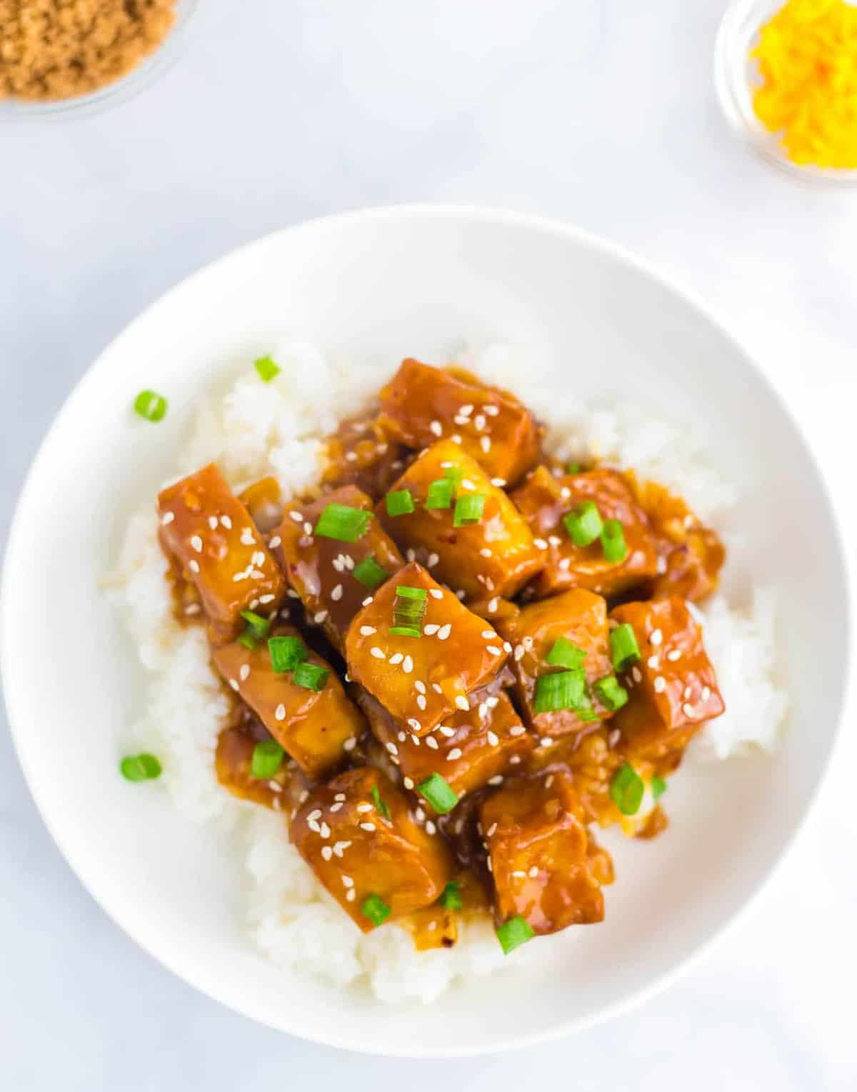 orange tofu in a bowl with white rice
