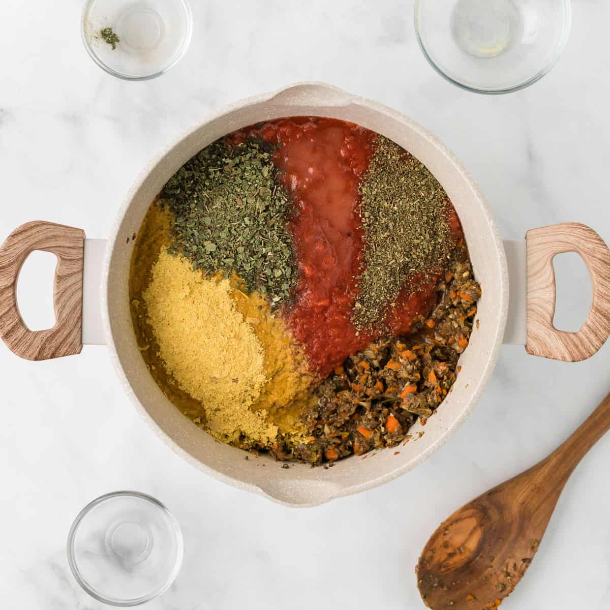 adding the nutritional yeast, tomatoes, and spices to the vegetarian bolognese