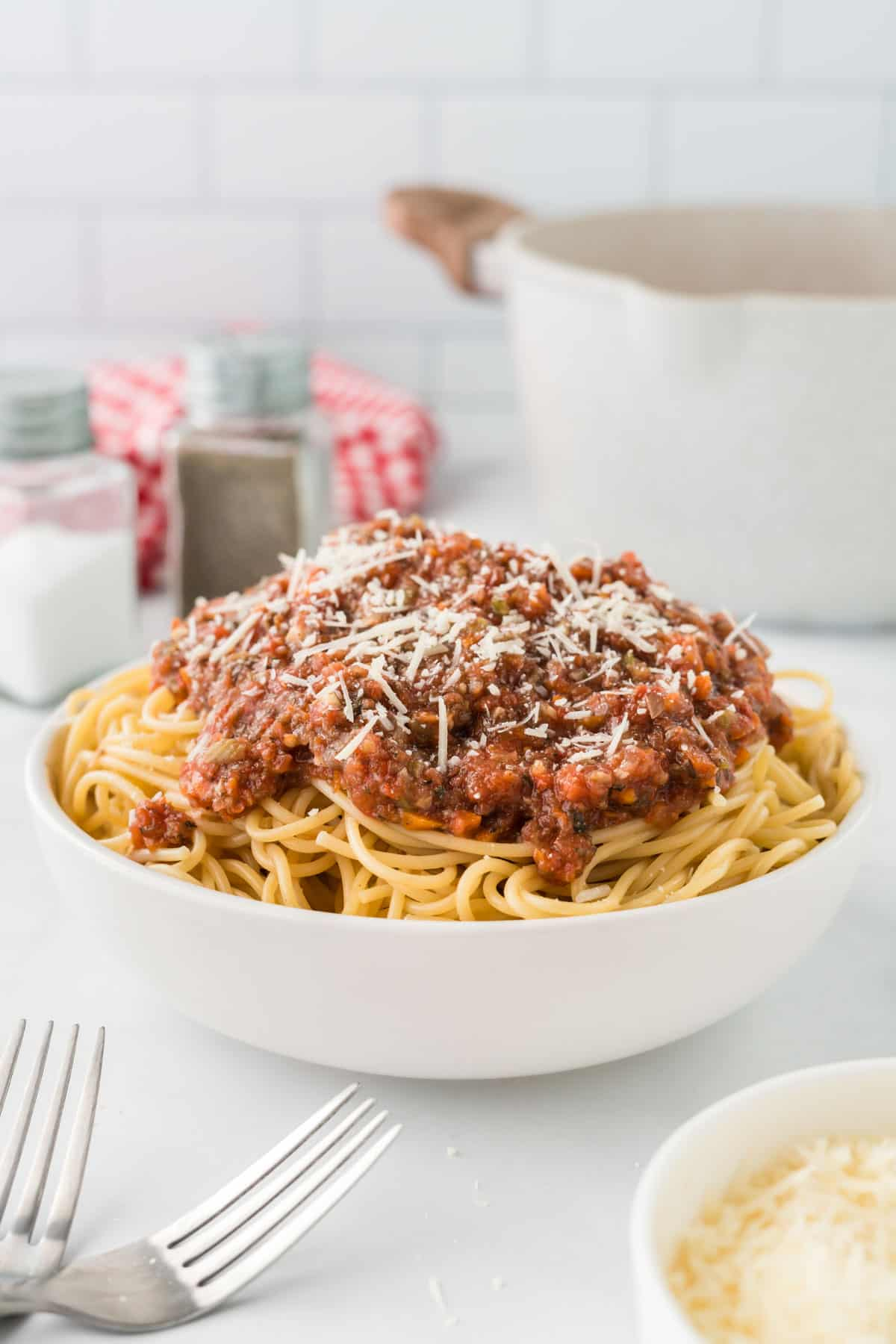 bowl of spaghetti topped with vegetarian bolognese sauce and parmesan cheese