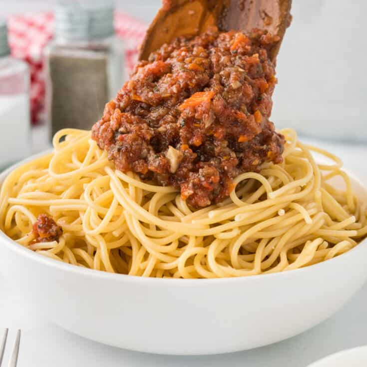 wooden spoon adding bolognese sauce to a bowl of spaghetti noodles