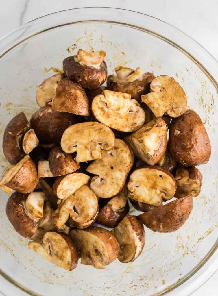 mushrooms in a bowl mixed with the seasoning ingredients before cooking