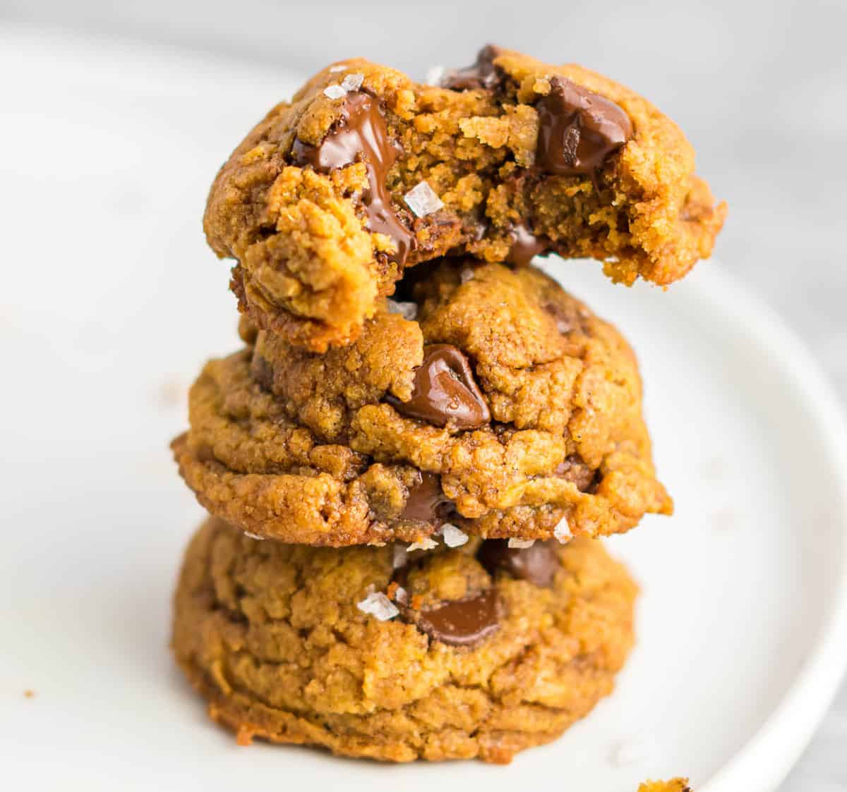 vegan pumpkin chocolate chip cookie with a bite taken out stacked on two cookies