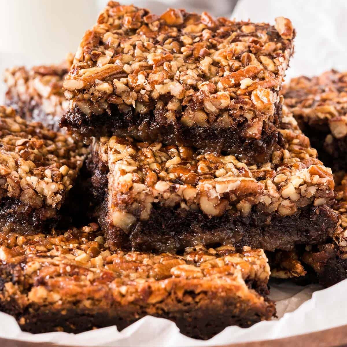 pecan pie brownies cut into squares and stacked on a plate