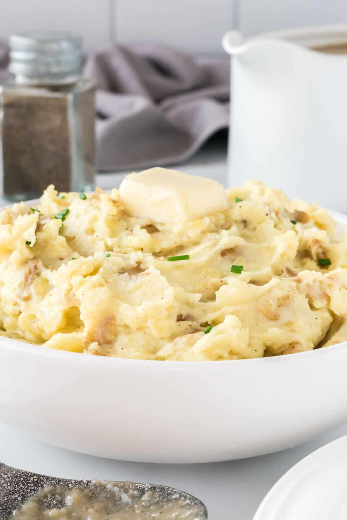mashed potatoes in a bowl topped with butter and chives