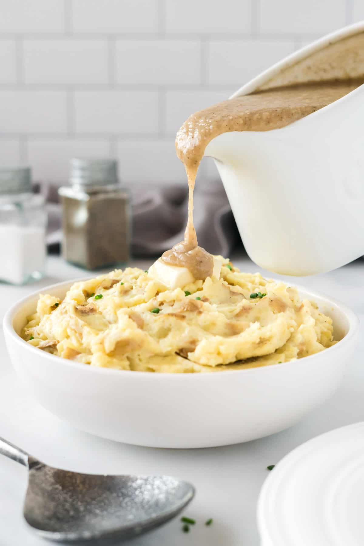 gravy being poured onto sour cream mashed potatoes