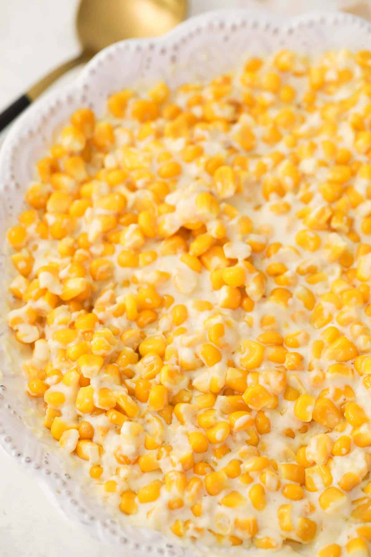 creamed corn with cream cheese in a white serving dish