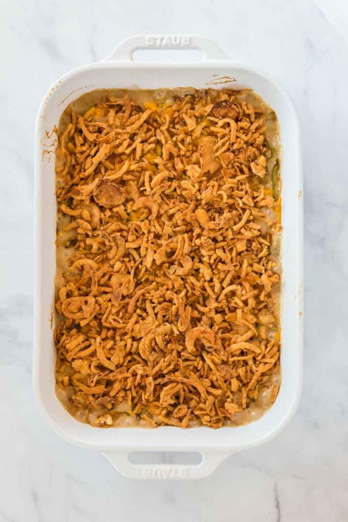 green bean casserole topped with golden french fried onions in a white baking dish