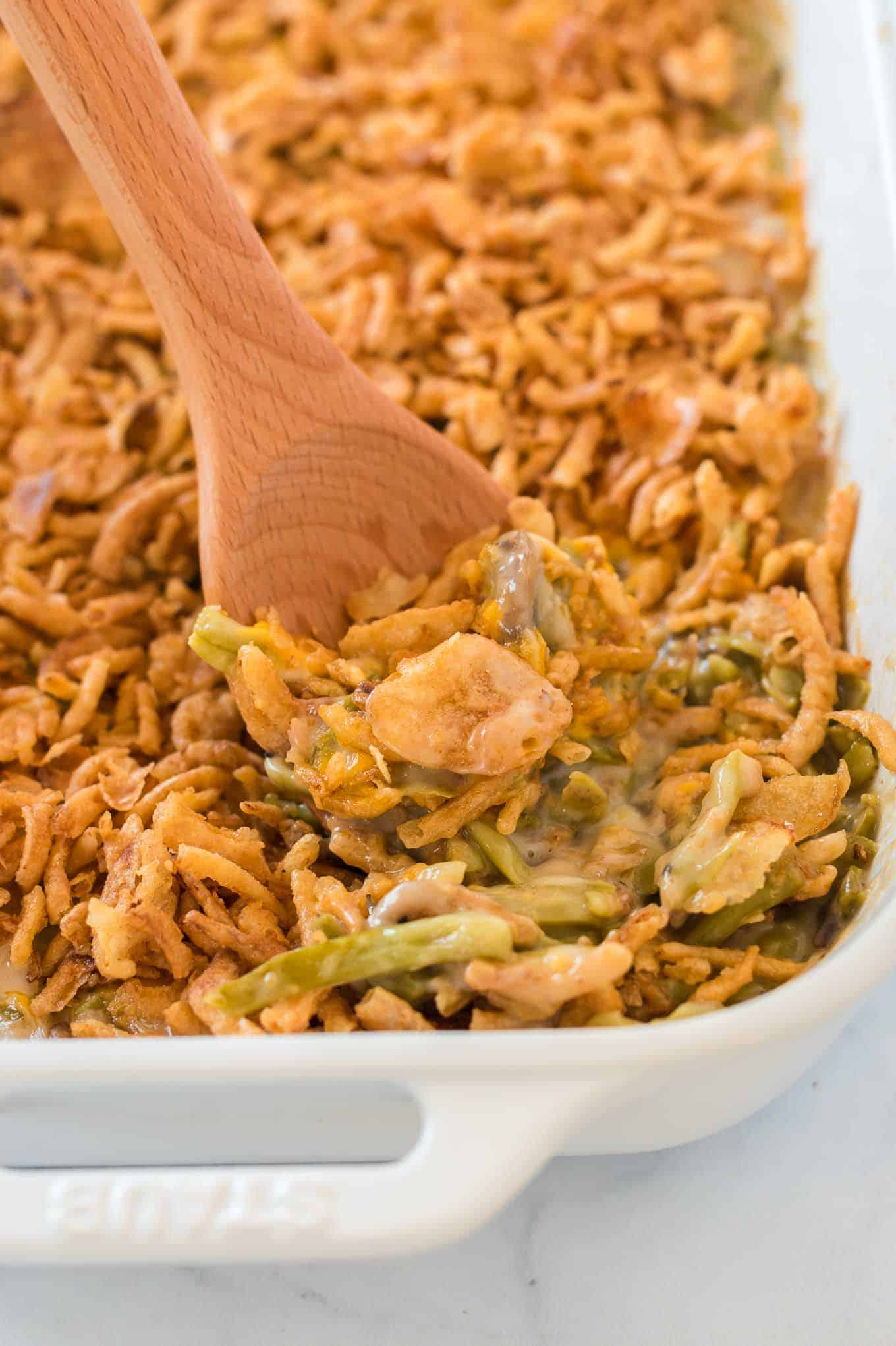 green bean casserole with a wooden spoon taking a scoop out