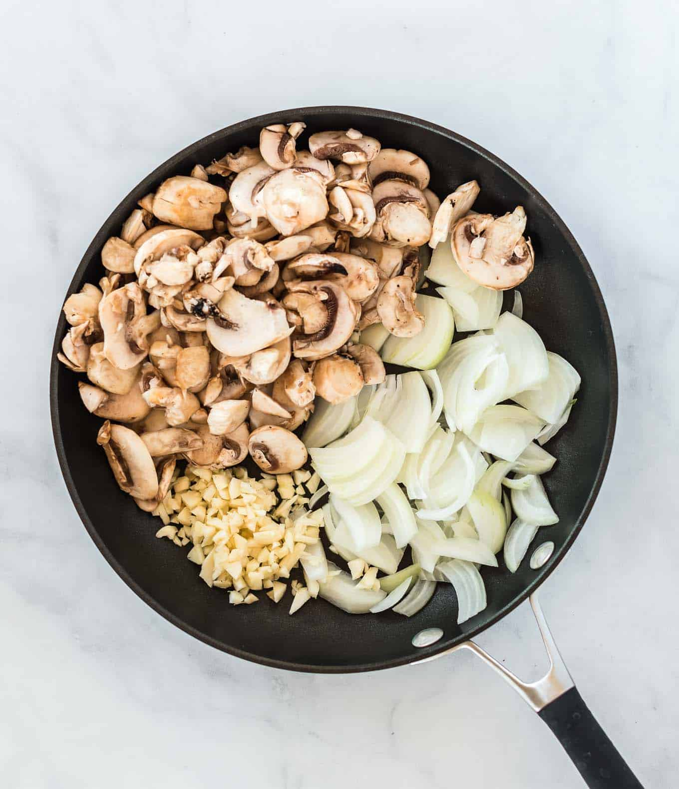 a skillet with mushrooms, minced garlic, and chopped onion in it