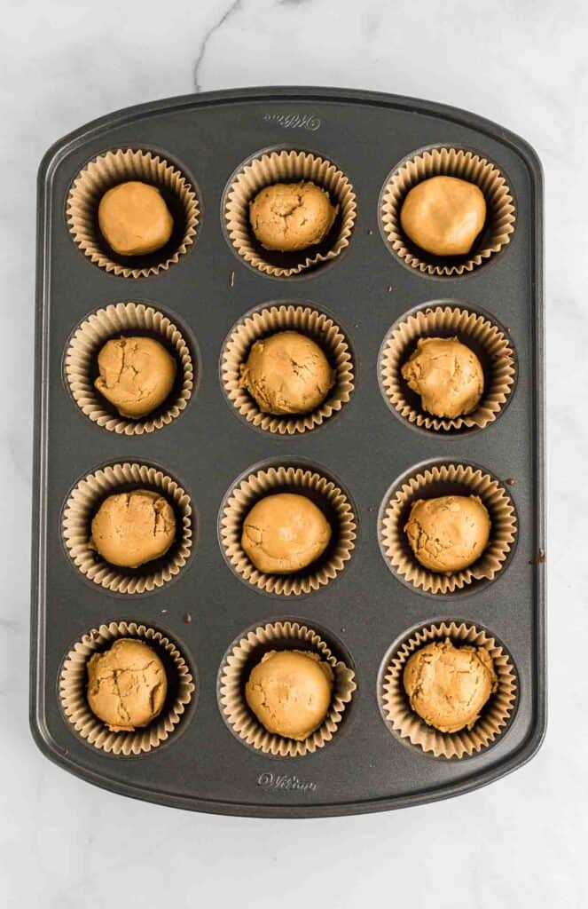 a muffin tin with the first chocolate layer topped with the peanut butter filling