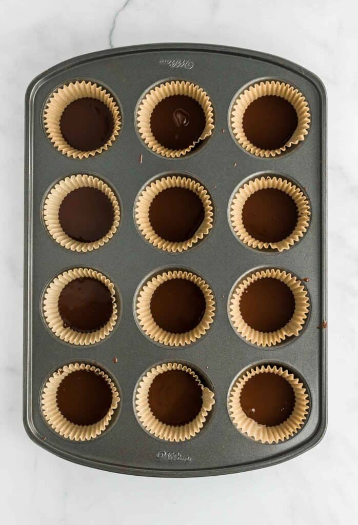 a muffin tin with each cup filled with the first layer of chocolate