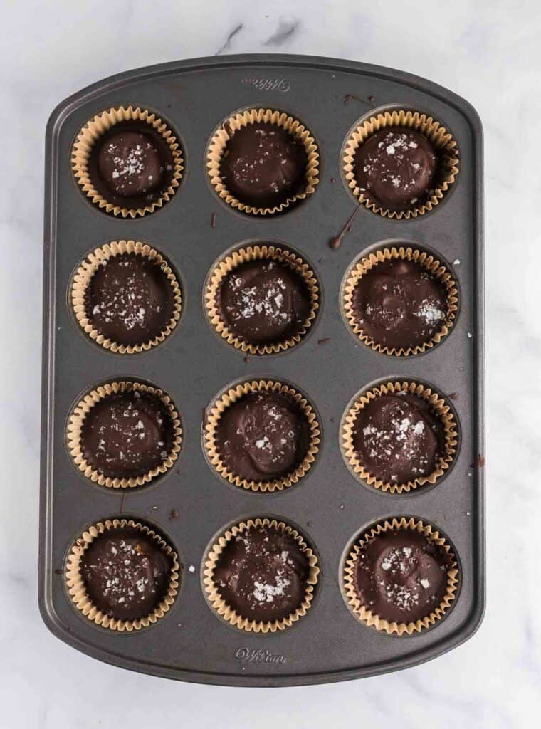 a muffin tin with the finished protein peanut butter cups