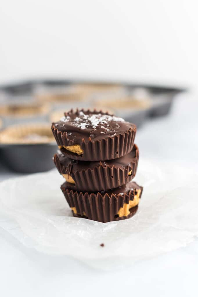 three peanut butter cups stacked with a muffin tin in the background