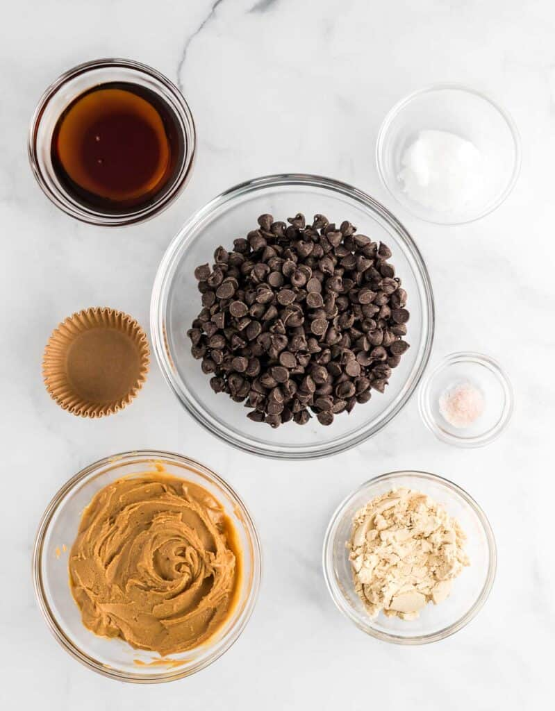 the ingredients in separate glass bowls - maple syrup, coconut oil, salt, protein powder, peanut butter, and chocolate chips