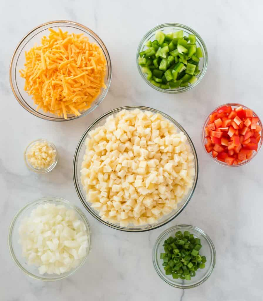 ingredients in separate glass bowls (potatoes, garlic, onion, bell pepper, cheese, green onions)