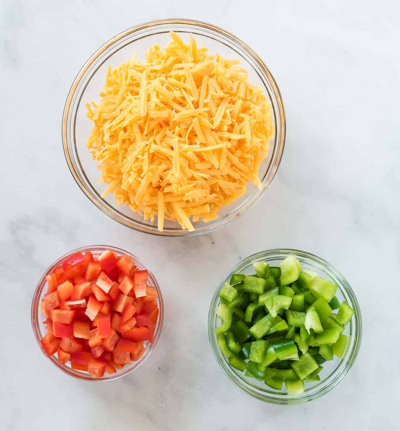 cheese, red bell pepper, and green bell pepper in separate glass bowls
