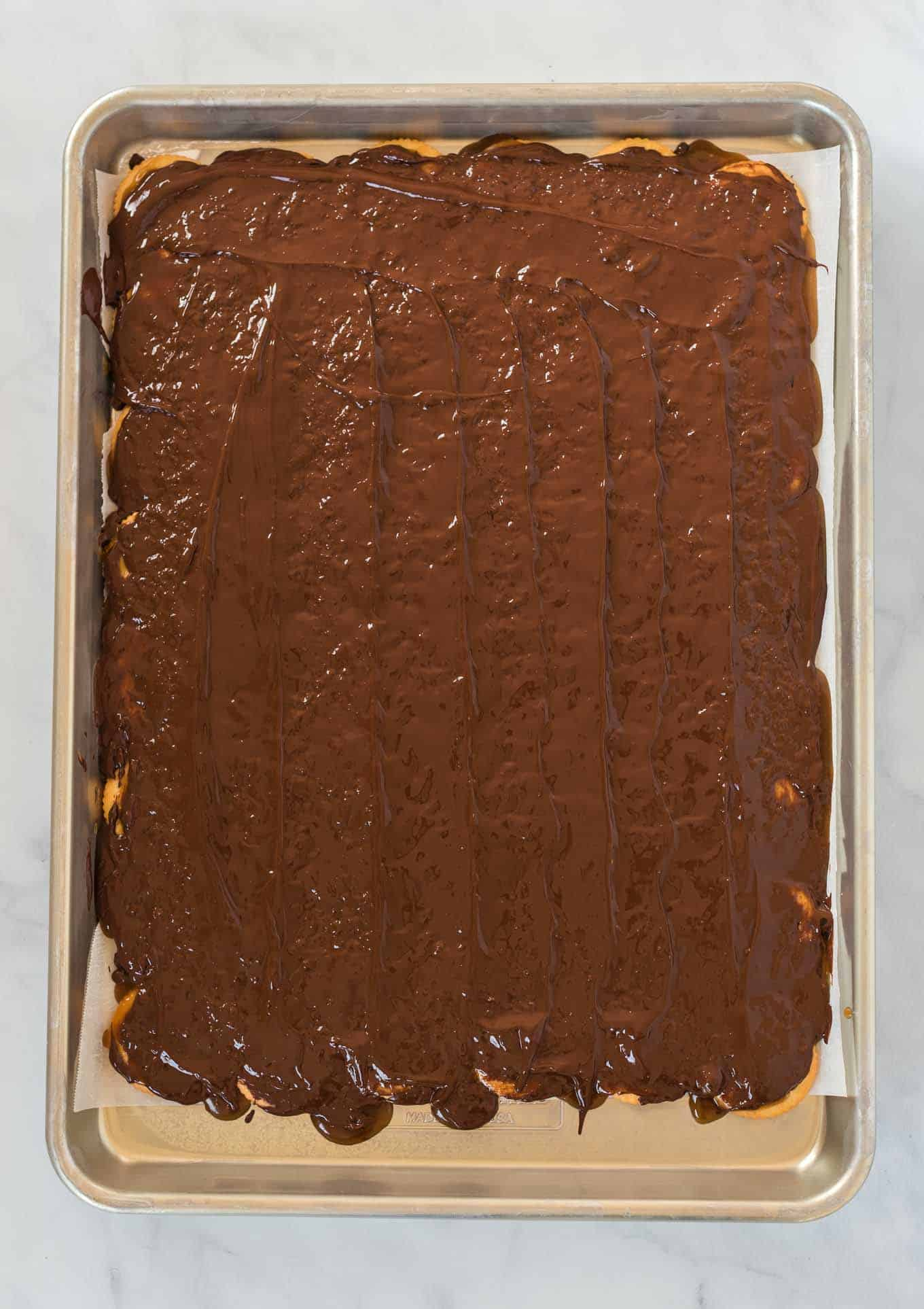 baking sheet lined with ritz crackers covered in melted chocolate