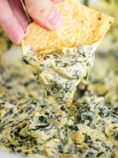 tortilla chip being dipped in spinach artichoke dip
