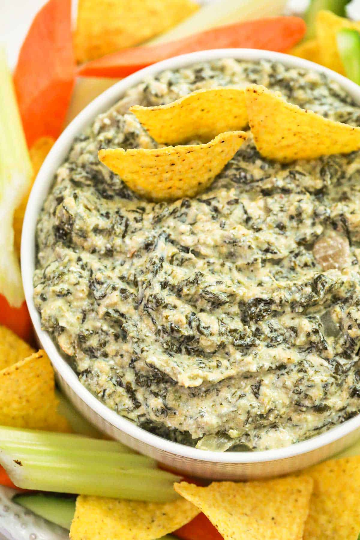 a bowl full of spinach artichoke dip with tortilla chips on the side