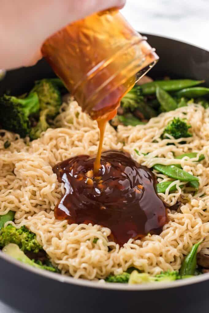 teriyaki sauce being poured onto a stir fry