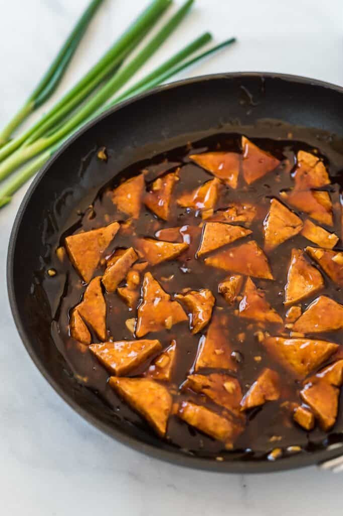 tofu triangles in teriyaki sauce in a skillet