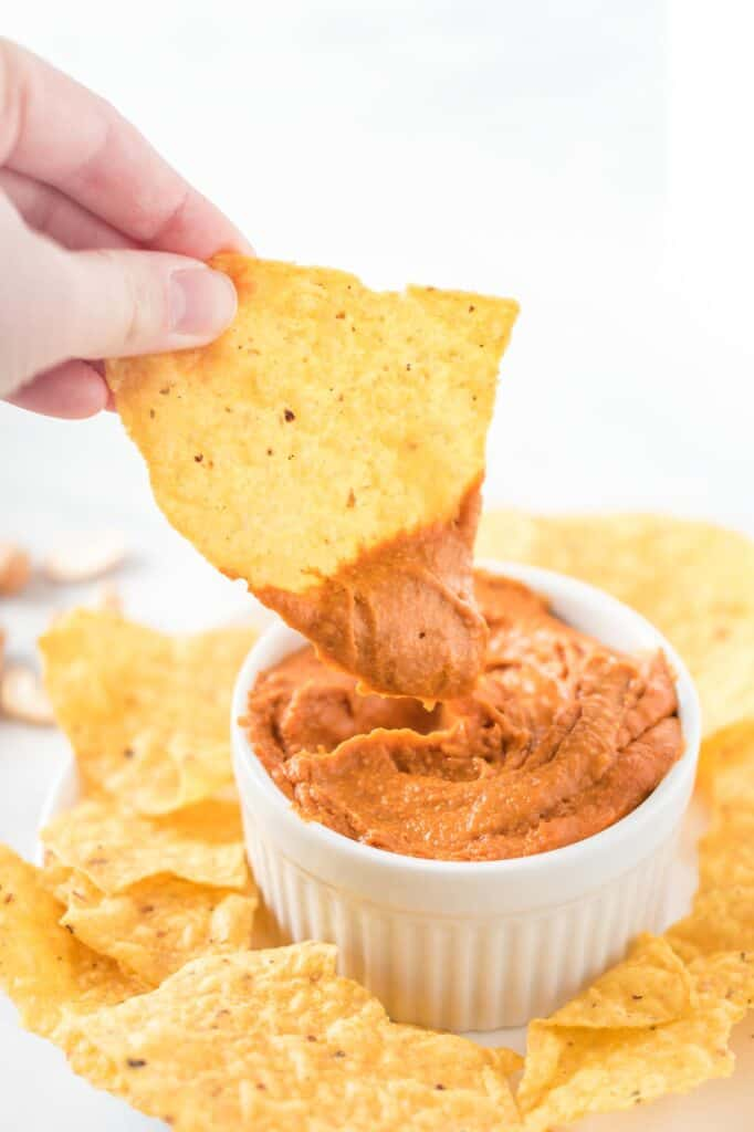 a chip dipped in a white ramekin of vegan queso