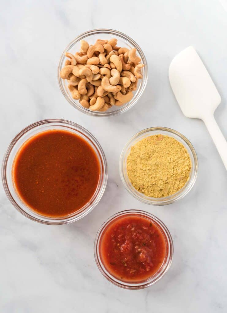 the ingredients in separate glass bowls (cashews, nutritional yeast, salsa, and enchilada sauce)