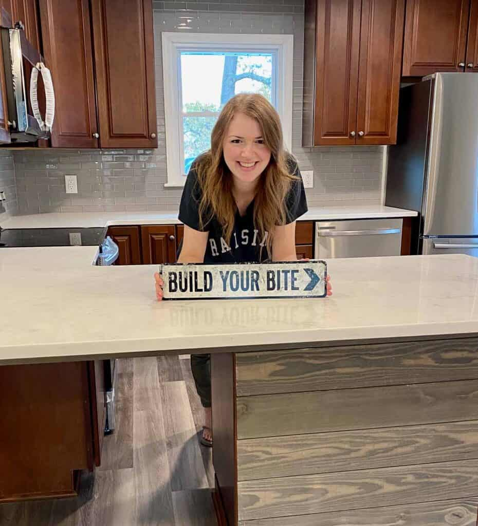 joy standing in her kitchen with a sign reading build your bite