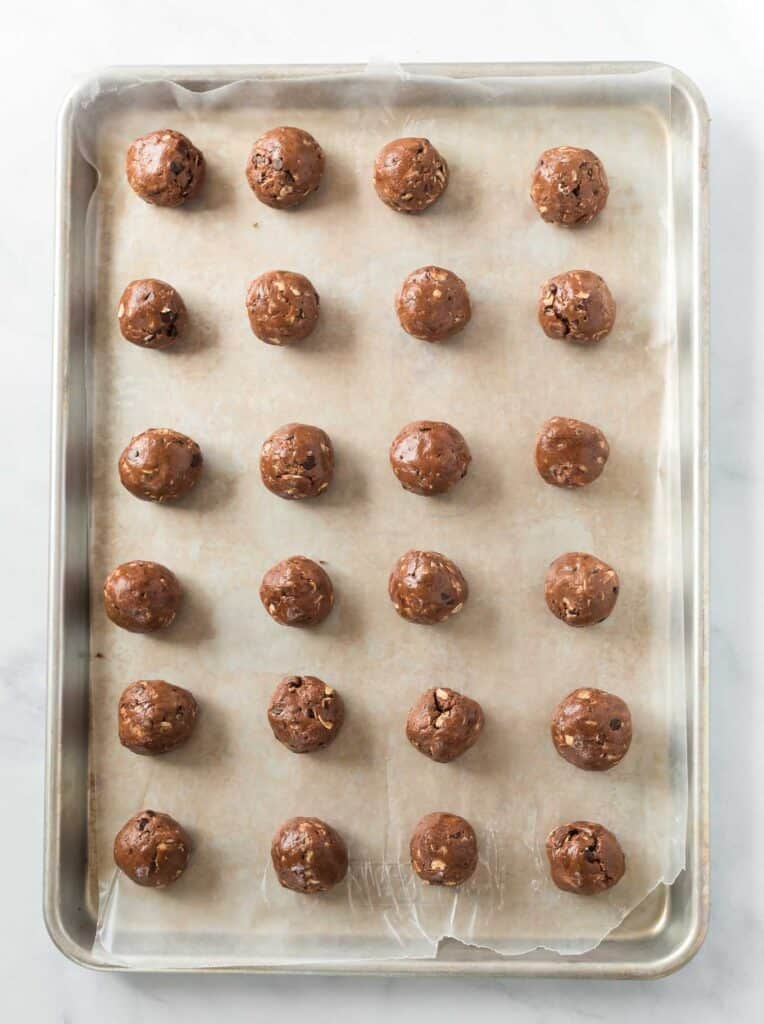 protein balls lined up on a wax paper lined baking sheet