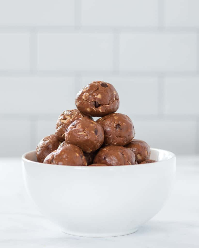 protein balls stacked in a white bowl