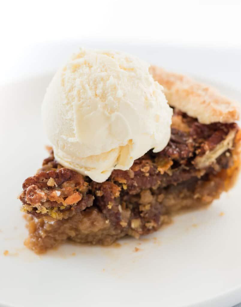 slice of pecan pie with a scoop of vanilla ice cream