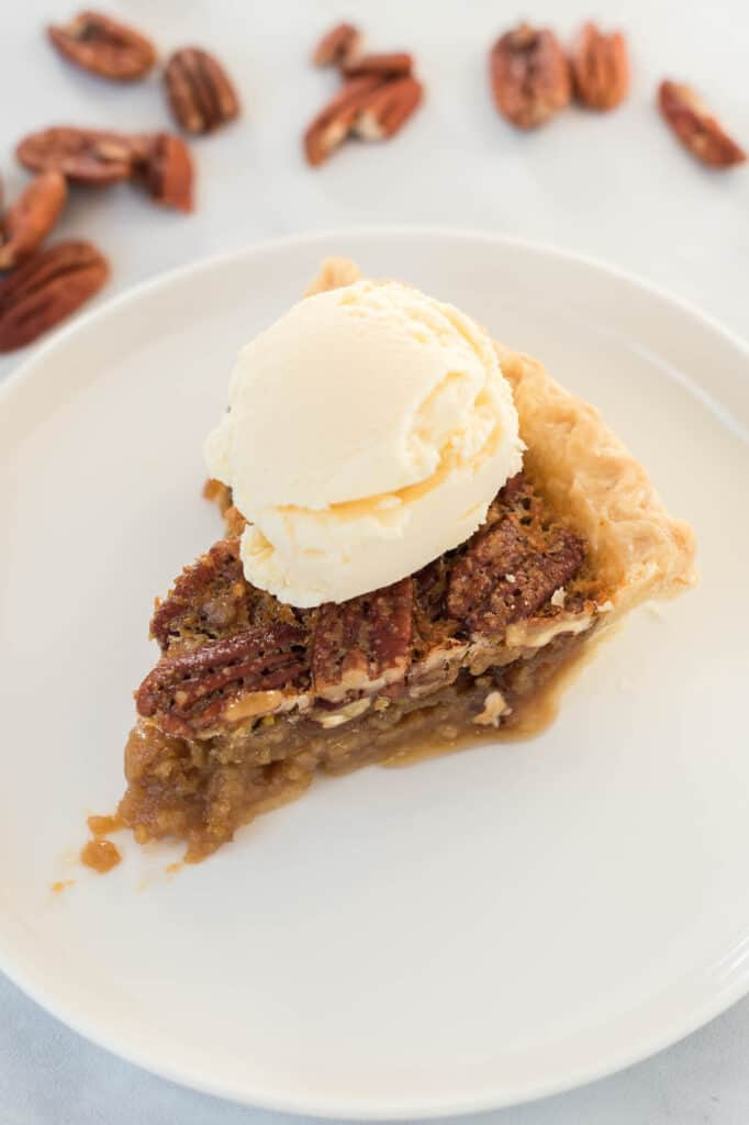 pecan pie without corn syrup on a white plate with a scoop of ice cream on top
