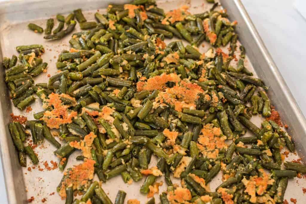 roasted green beans with parmesan on a baking sheet