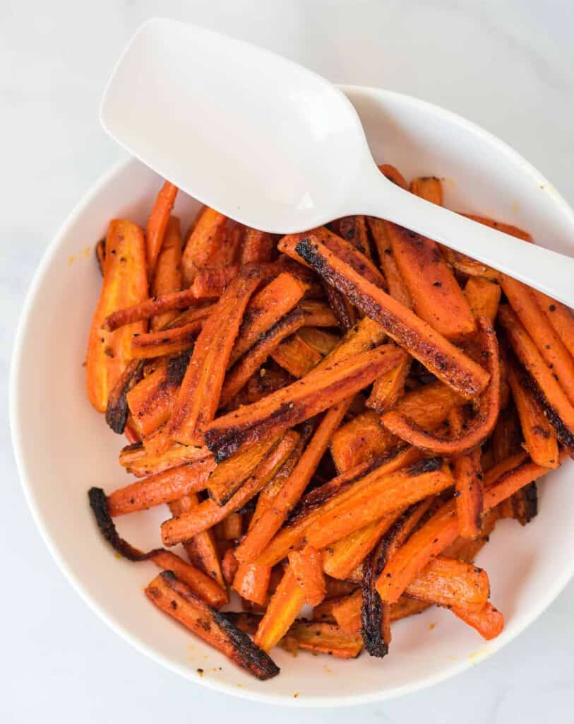 roasted carrots in a white bowl with a spoon