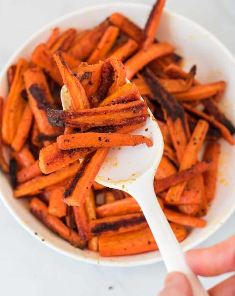 a spoon scooping roasted carrots from a bowl