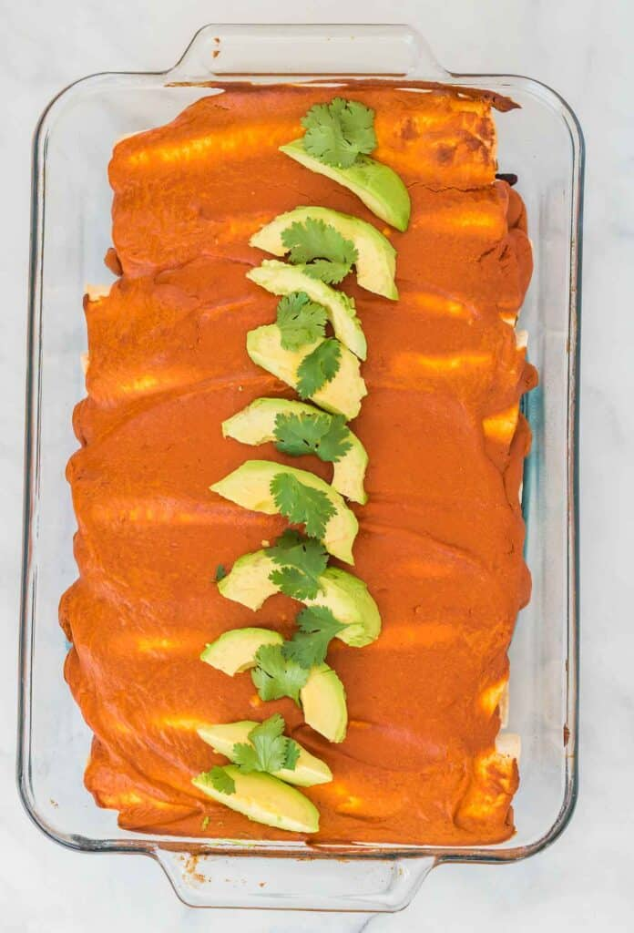 baked vegan enchiladas topped with sliced avocado and cilantro