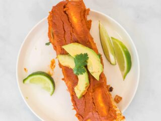 two enchiladas on a white plate topped with avocado and cilantro, with limes on the side