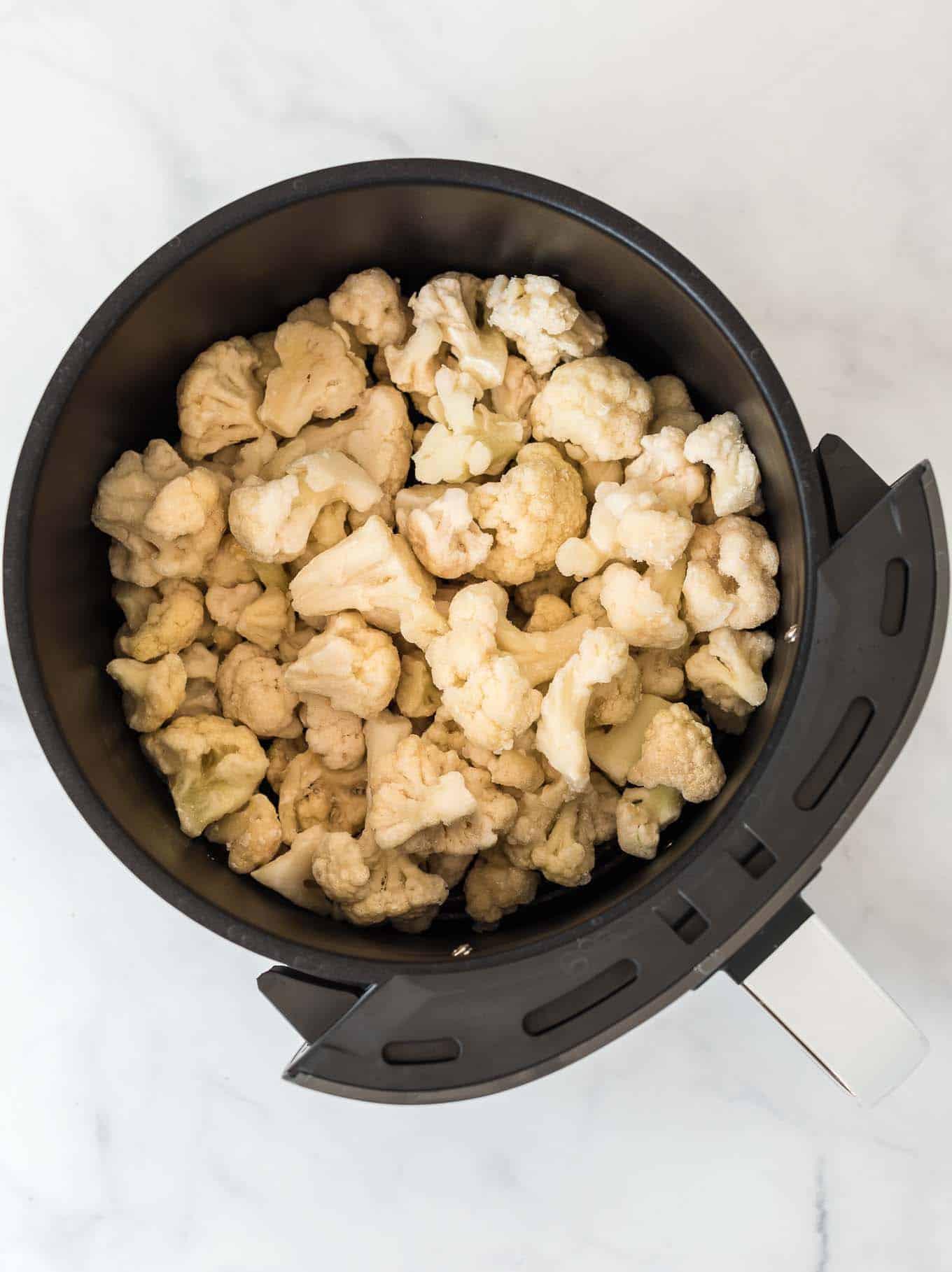 frozen cauliflower in an air fryer basket