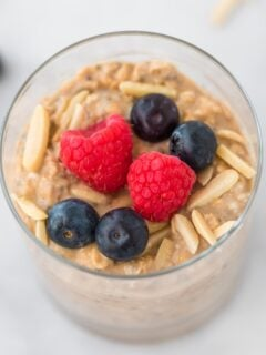protein overnight oats in a clear glass topped with slivered almonds, raspberries, and blueberries