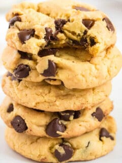 stacked chocolate chip cookies with one taken a bite out of
