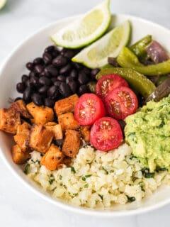 cauliflower rice burrito bowl with sweet potato, black bean, guacamole, tomatoes, and fajita veggies