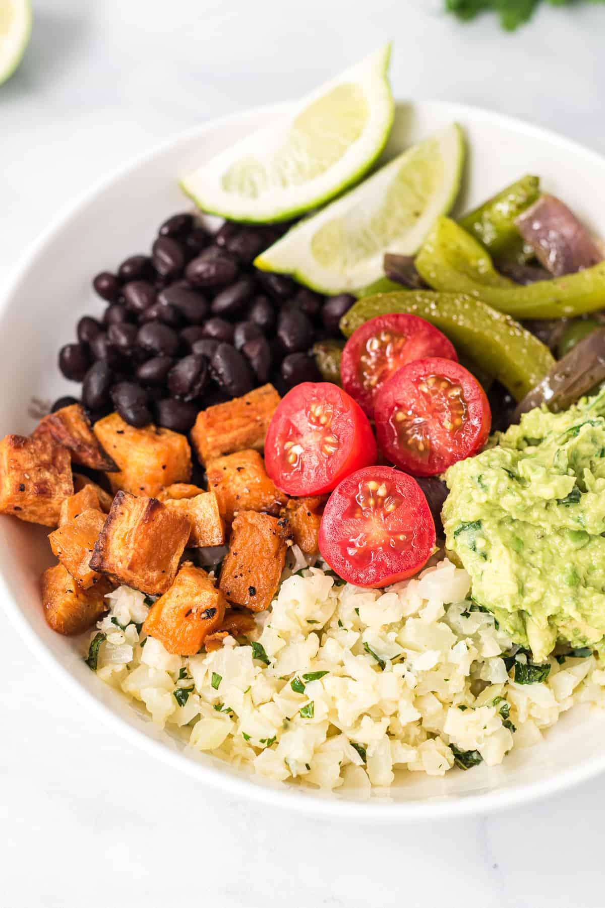 cauliflower rice burrito bowl with sweet potatoes, tomatoes, guacamole, fajita veggies, and black beans