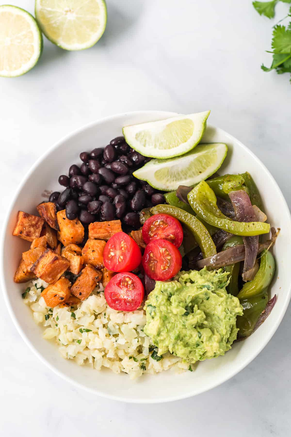 burrito bowl with sweet potatoes, black beans, tomatoes, guacamole, fajita veggies, and lime wedges
