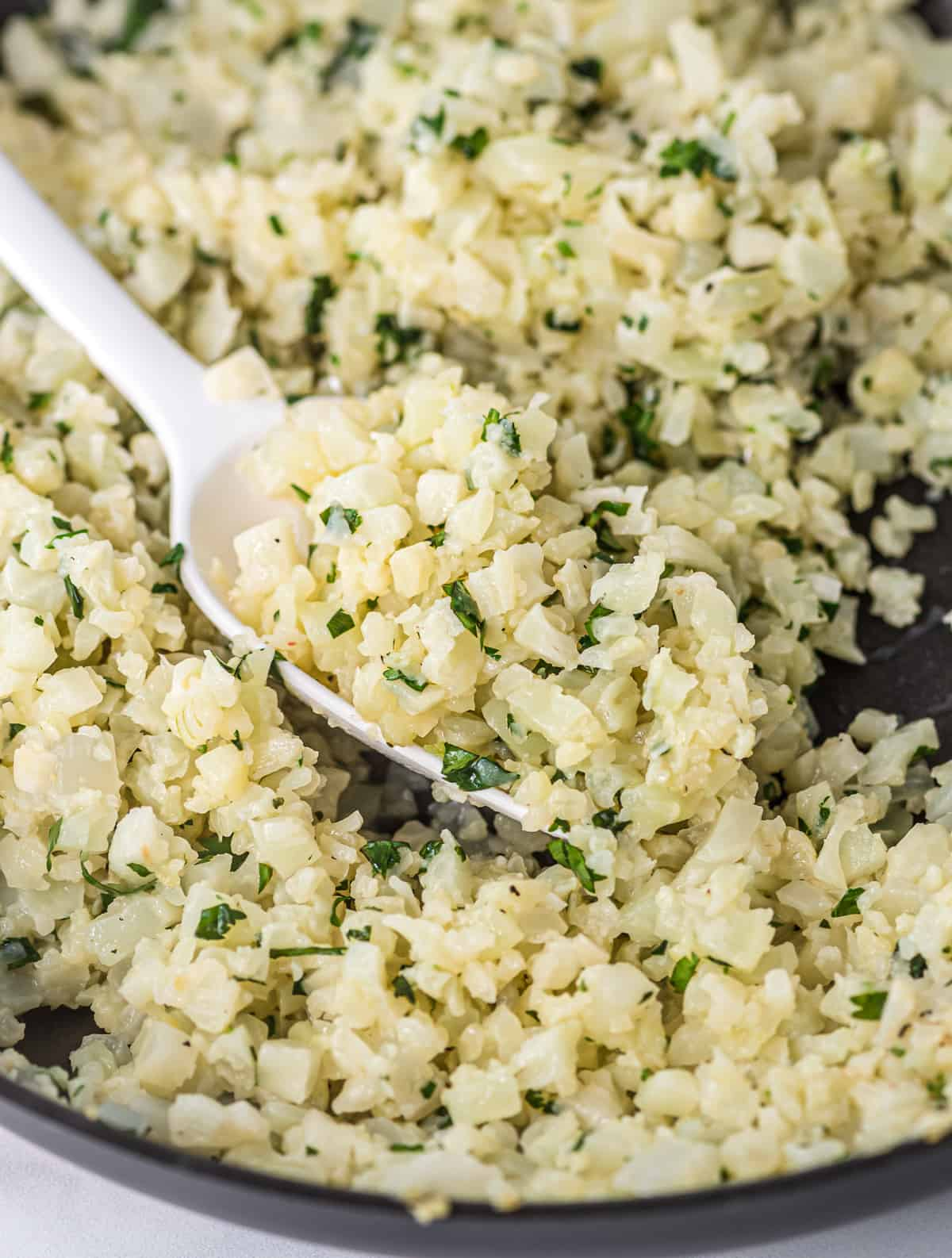 a white spoon taking a scoop of cauliflower rice from the skillet